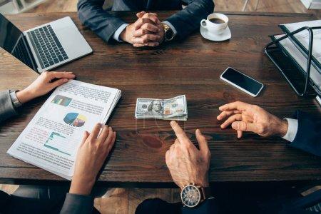 Photo pour Vue recadrée de l'homme d'affaires pointant vers l'argent près d'un collègue avec des papiers et des appareils sur la table - image libre de droit