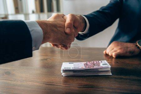 Photo pour Vue recadrée des billets en euros sur la table et des hommes d'affaires serrant la main sur le premier plan flou au bureau - image libre de droit