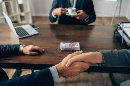 Photo pour Vue recadrée des partenaires commerciaux serrant la main près de l'argent et collègue avec tasse sur fond flou - image libre de droit