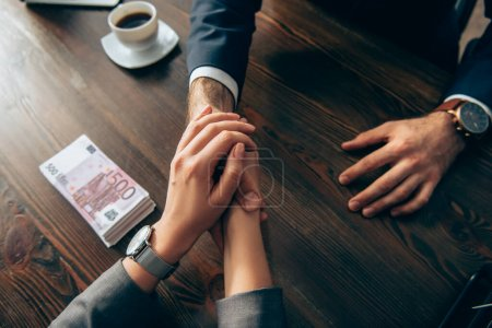 Cropped view of business people shaking hands near euro banknotes and coffee on blurred background