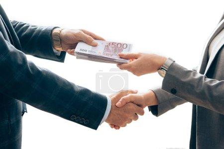 Photo pour Vue recadrée de l'investisseur donnant de l'argent et poignée de main avec femme d'affaires isolée sur blanc - image libre de droit
