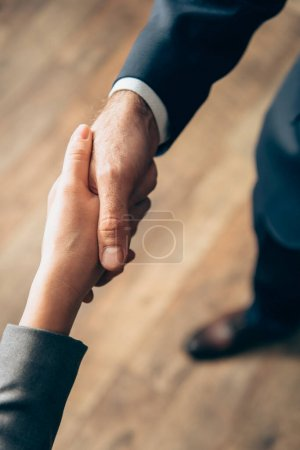Photo for Cropped view of business people handshaking in office - Royalty Free Image