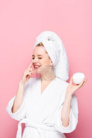 glücklich junge Frau im Bademantel Handtuch auf dem Kopf hält kosmetische Creme und trägt sie auf die Nase isoliert auf rosa