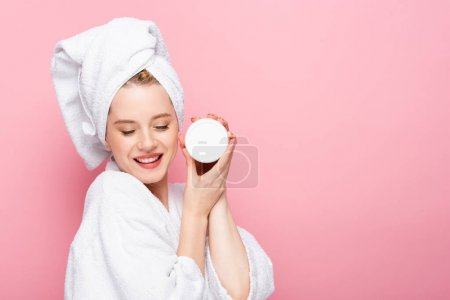 Photo for Happy young woman in bathrobe with closed eyes, towel on head holding cosmetic cream isolated on pink - Royalty Free Image