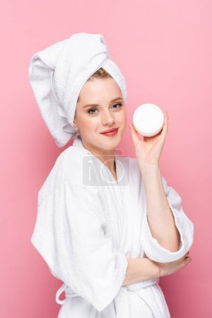 young woman in bathrobe with towel on head holding cosmetic cream isolated on pink