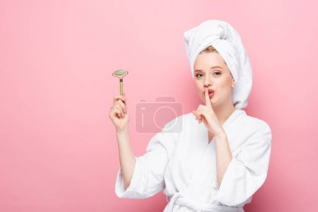 young woman in bathrobe with towel on head holding jade roller and showing shh isolated on pink