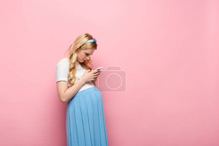 Photo for Blonde young pregnant woman using smartphone on pink background - Royalty Free Image
