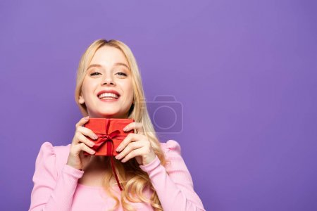 happy blonde young woman holding red gift box on purple background
