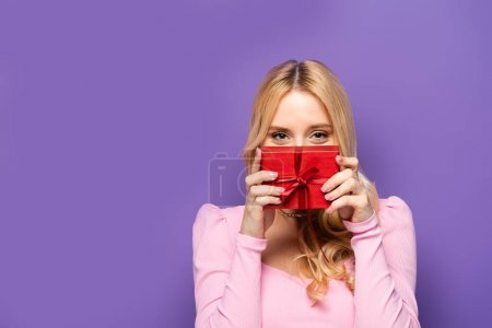 blonde young woman holding red gift box near face on purple background