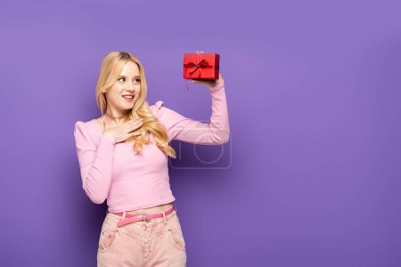 Photo for Happy blonde young woman holding red gift box on purple background - Royalty Free Image