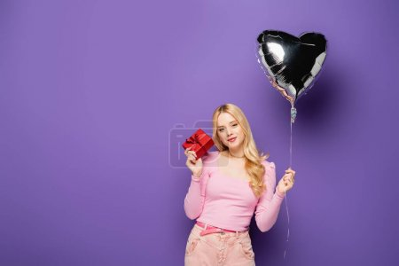 blonde young woman holding heart shaped balloon and gift on purple background