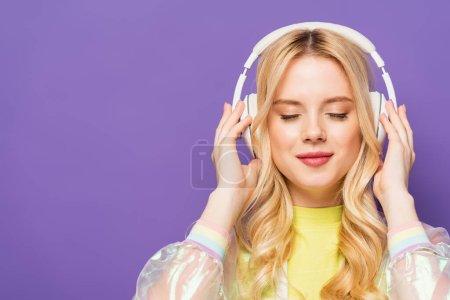 Photo pour Blonde jeune femme en tenue colorée et écouteurs avec les yeux fermés isolé sur violet - image libre de droit