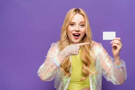 shocked blonde young woman in colorful outfit pointing at blank card on purple background