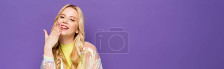 Photo for Smiling blonde young woman in colorful outfit with hand near face on purple background, banner - Royalty Free Image
