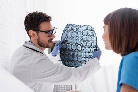 Photo pour Médecin souriant montrant la radiographie à la fille sur le premier plan flou - image libre de droit