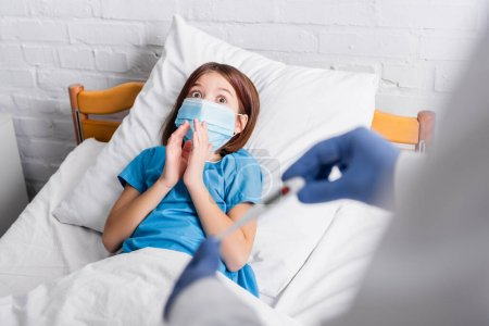 shocked girl in medical mask showing pray gesture near pediatrician with thermometer on blurred foreground