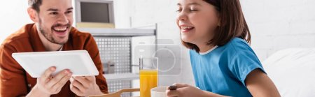 Photo pour Excited man with daughter laughing during breakfast in hospital, banner - image libre de droit
