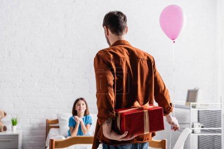 Photo pour Vue arrière de l'homme tenant ballon festif et boîte cadeau près de fille heureuse sur fond flou - image libre de droit