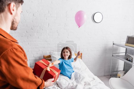 man holding gift box near happy daughter on hospital bed with festive balloon, blurred foreground