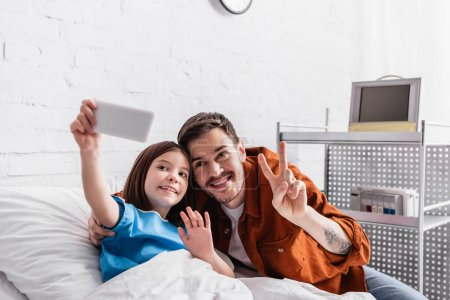 happy man showing victory gesture near daughter waving hand while taking selfie on smartphone, blurred foreground