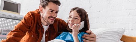 happy girl talking on mobile phone in hospital near happy father, banner