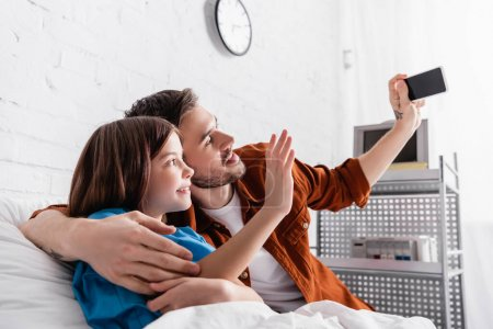 Photo for Cheerful man taking selfie on smartphone with daughter in hospital - Royalty Free Image