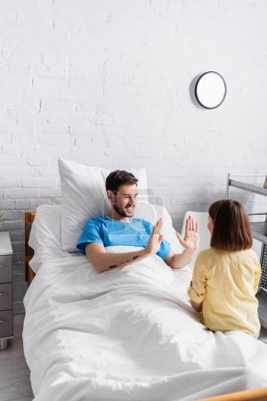 cheerful man playing patty-cake game with daughter in hospital