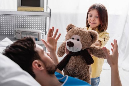 smiling girl giving teddy bear to father lying in hospital