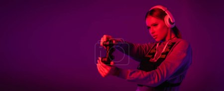 Photo for KYIV, UKRAINE - NOVEMBER 27, 2020: young woman in headphones playing video game on purple background, banner - Royalty Free Image