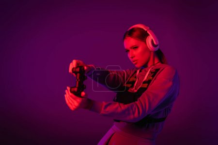 KYIV, UKRAINE - NOVEMBER 27, 2020: young woman in headphones playing video game on purple background