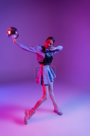 Photo for Full length of woman in skirt holding disco balls on purple - Royalty Free Image