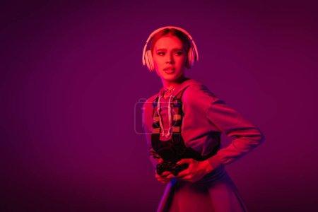 Photo for KYIV, UKRAINE - NOVEMBER 27, 2020: woman in wireless headphones holding joystick on purple background - Royalty Free Image