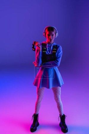 KYIV, UKRAINE - 27 NOVEMBRE 2020 : toute la longueur de la femme dans les écouteurs sans fil tenant une manette de jeu sur violet