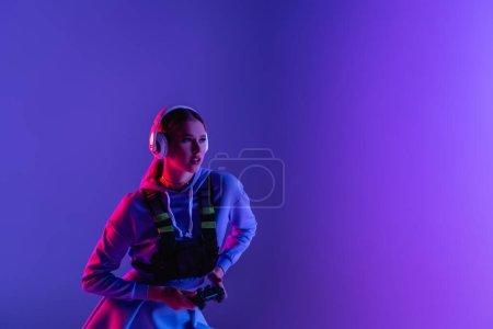 KYIV, UKRAINE - NOVEMBER 27, 2020: woman in wireless headphones holding gamepad and playing video game on purple