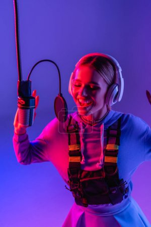 happy woman in wireless headphones recording song while singing in microphone on purple with color filter