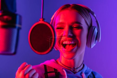 young singer in wireless headphones recording song while singing in microphone on blurred foreground