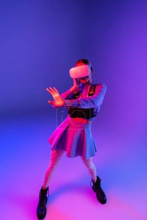 Photo pour Pleine longueur de jeune femme en réalité virtuelle casque geste sur fond violet - image libre de droit