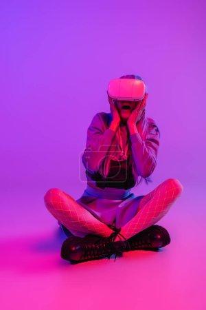 Photo pour Pleine longueur de femme effrayée en réalité virtuelle casque assis sur fond violet - image libre de droit