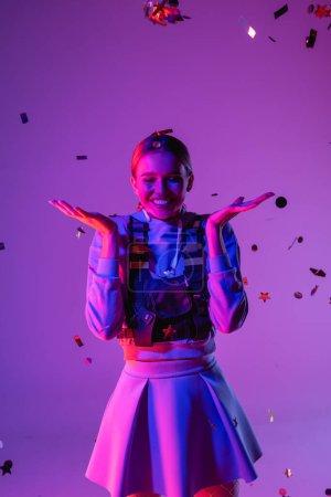 joyful woman in stylish outfit near falling confetti on purple