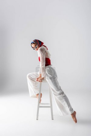 Photo for Full length of stylish woman in headscarf and sunglasses posing on stool while looking at camera on white - Royalty Free Image