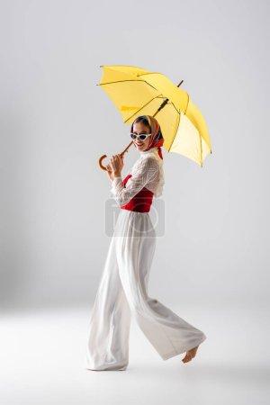 longitud completa de mujer feliz en pañuelo para la cabeza y gafas de sol sosteniendo paraguas amarillo mientras posando en blanco