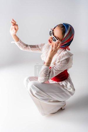 Photo pour Femme élégante en foulard ajustant les lunettes de soleil, gestuelle et assise sur blanc - image libre de droit