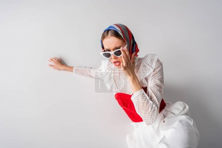 high angle view of young trendy woman in headscarf touching sunglasses on white
