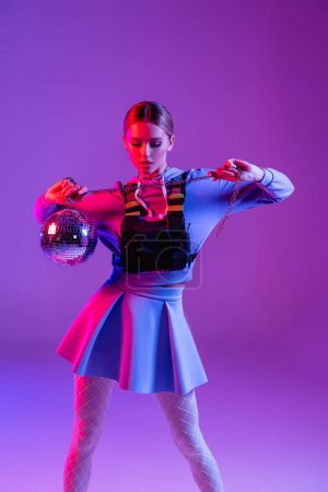 young and stylish woman in skirt posing with shiny disco ball on purple