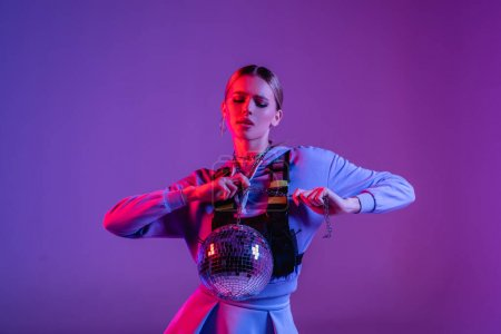 young and stylish woman posing with shiny disco ball on purple