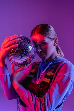 young and stylish woman holding shiny disco ball and looking at camera isolated on purple