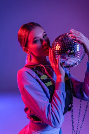young and stylish woman holding shiny disco ball on purple