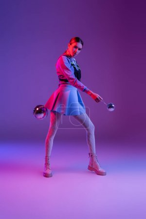 full length of fashionable woman in skirt holding disco balls on purple