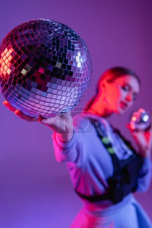 party disco ball in hand of trendy woman on purple and blurred background