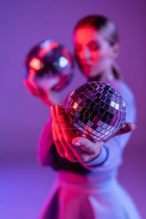 shiny disco ball in hand of trendy woman on purple and blurred background